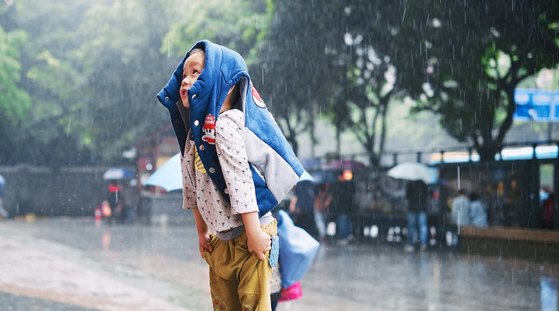 criança brincando na chuva