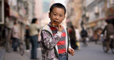 criança comendo carne na china