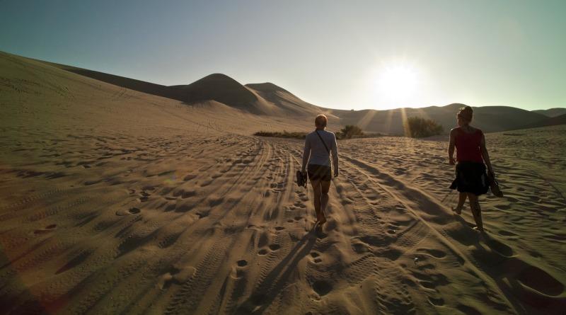Pessoas caminham em dunas no deserto