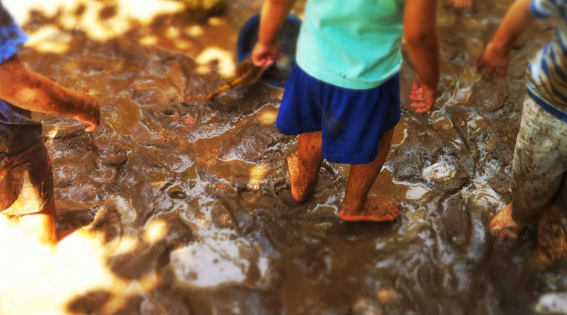 criança brincando na lama
