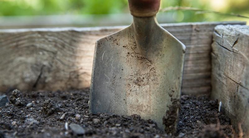 pá enterrada na terra do jardim
