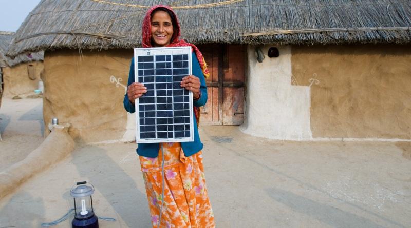 investimento recorde em energia renovável - mulher com painel solar na Índia