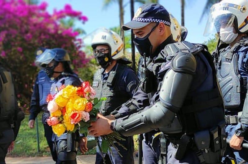 Em ato pacífico pelo arquivamento do PL 490, em frente à Câmara dos Deputados, mulheres indígenas entregam flores para policiais